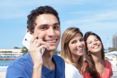 stock-photo-70901761-mexican-guy-talking-at-phone-with-two-girlfriends-in-background